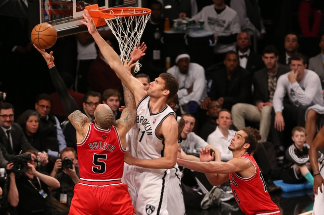 Apr 22, 2013; Brooklyn, NY, USA;  Brooklyn Nets center Brook Lopez (11) and Chicago Bulls power forward Carlos Boozer (5) battle at the net during the fourth quarter of game two in the first round of the 2013 NBA playoffs at the Barclays Center. Chicago won 90-82.  Mandatory Credit: Anthony Gruppuso-USA TODAY Sports