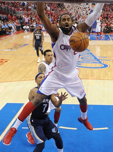 Apr 22, 2013; Los Angeles, CA, USA; Los Angeles Clippers center Ronny Turiaf (21) dunks in front of Memphis Grizzlies point guard Jerryd Bayless (7) during game one in the first round of the 2013 NBA playoffs at the Staples Center. Clippers won 93-91. Mandatory Credit: Jayne Kamin-Oncea-USA TODAY Sports