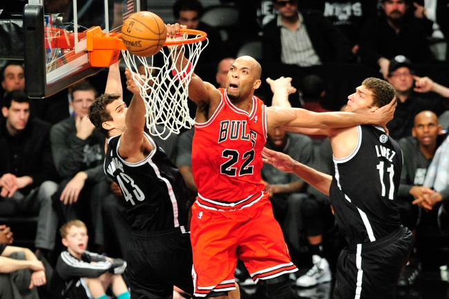 Apr 20, 2013; Brooklyn, NY, USA; Chicago Bulls power forward Taj Gibson (22) attempts a dunk and is fouled by Brooklyn Nets power forward Kris Humphries (43) during the second half of game one of the first round of the 2013 NBA Playoffs at the Barclays Center. The Nets won the game 106-89. Mandatory Credit: Joe Camporeale-USA TODAY Sports
