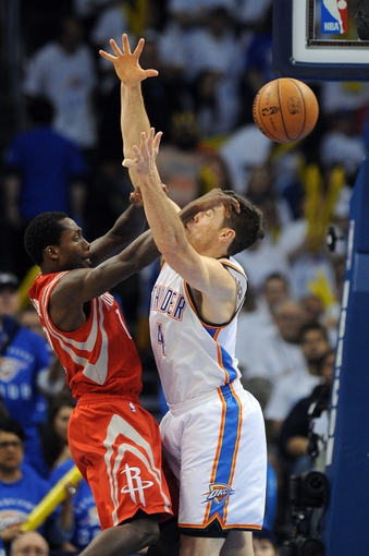 Apr 24, 2013; Oklahoma City, OK, USA; Houston Rockets guard Patrick Beverly (12) passes the ball against Oklahoma City Thunder forward Nick Collison (4) in the second half during game two of the first round of the 2013 NBA Playoffs at Chesapeake Energy Arena. Mandatory Credit: Mark D. Smith-USA TODAY Sports