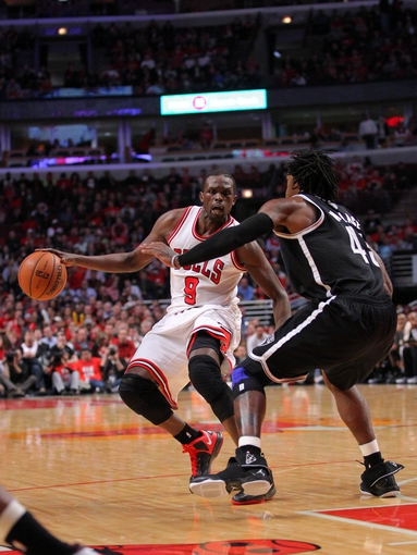 Apr 25, 2013; Chicago, IL, USA; Chicago Bulls small forward Luol Deng (9) is defended by Brooklyn Nets small forward Gerald Wallace (45) during the second quarter of the first round of the 2013 NBA playoffs at the United Center. Mandatory Credit: Dennis Wierzbicki-USA TODAY Sports
