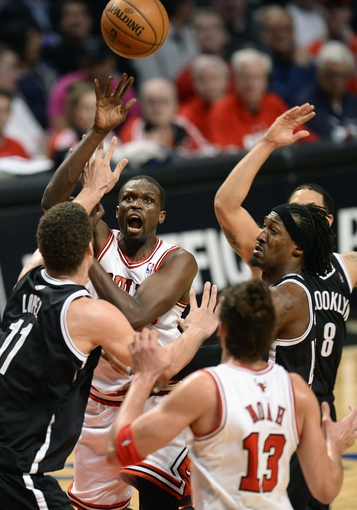 Apr 25, 2013; Chicago, IL, USA; Chicago Bulls small forward Luol Deng (9) shoots the ball over Brooklyn Nets center Brook Lopez (11) in the second half during game three of the first round of the 2013 NBA playoffs at the United Center. Chicago defeats Brooklyn 79-76. Mandatory Credit: Mike DiNovo-USA TODAY Sports