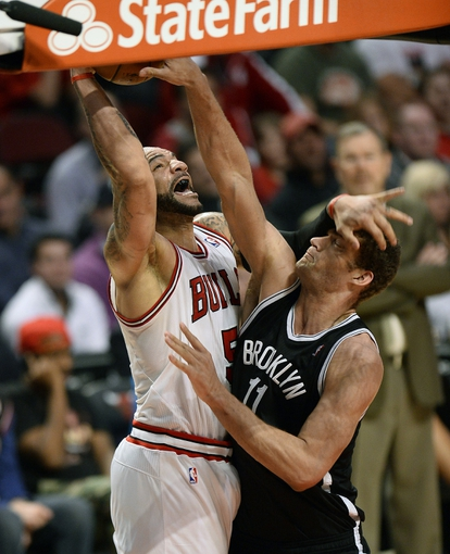 Apr 25, 2013; Chicago, IL, USA; Chicago Bulls power forward Carlos Boozer (5) shoots the ball over Brooklyn Nets center Brook Lopez (11) in the second half during game three of the first round of the 2013 NBA playoffs at the United Center. Chicago defeats Brooklyn 79-76. Mandatory Credit: Mike DiNovo-USA TODAY Sports