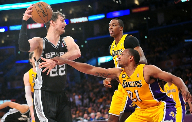 April 26, 2013; Los Angeles, CA, USA; San Antonio Spurs center Tiago Splitter (22) controls the ball against the defense of Los Angeles Lakers center Dwight Howard (12) and point guard Chris Duhon (21) during the second half in game three of the first round of the 2013 NBA playoffs at Staples Center. Mandatory Credit: Gary A. Vasquez-USA TODAY Sports