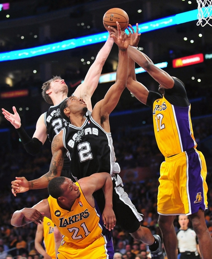 April 26, 2013; Los Angeles, CA, USA; San Antonio Spurs center Tiago Splitter (22) and small forward Kawhi Leonard (2) both play for the rebound against Los Angeles Lakers center Dwight Howard (12) during the second half in game three of the first round of the 2013 NBA playoffs at Staples Center. Mandatory Credit: Gary A. Vasquez-USA TODAY Sports