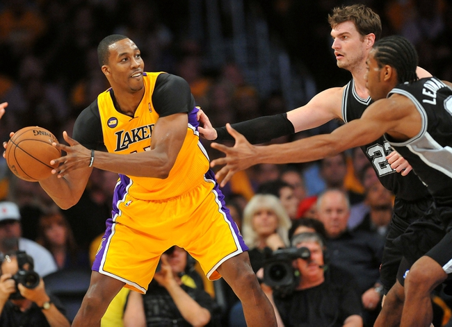 April 26, 2013; Los Angeles, CA, USA; Los Angeles Lakers  center Dwight Howard (12) controls the ball against the defense of San Antonio Spurs center Tiago Splitter (22) and small forward Kawhi Leonard (2) during the second half in game three of the first round of the 2013 NBA playoffs at Staples Center. Mandatory Credit: Gary A. Vasquez-USA TODAY Sports
