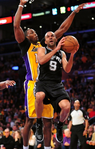 April 26, 2013; Los Angeles, CA, USA; San Antonio Spurs point guard Tony Parker (9) goes in for a basket against the defense of Los Angeles Lakers center Dwight Howard (12) during the second half in game three of the first round of the 2013 NBA playoffs at Staples Center. Mandatory Credit: Gary A. Vasquez-USA TODAY Sports