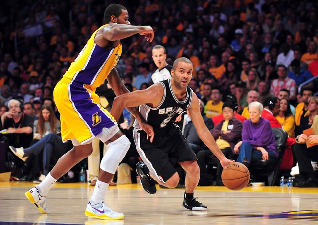 April 26, 2013; Los Angeles, CA, USA; San Antonio Spurs point guard Tony Parker (9) moves to the basket against the defense of Los Angeles Lakers small forward Earl Clark (6) during the second half in game three of the first round of the 2013 NBA playoffs at Staples Center. Mandatory Credit: Gary A. Vasquez-USA TODAY Sports