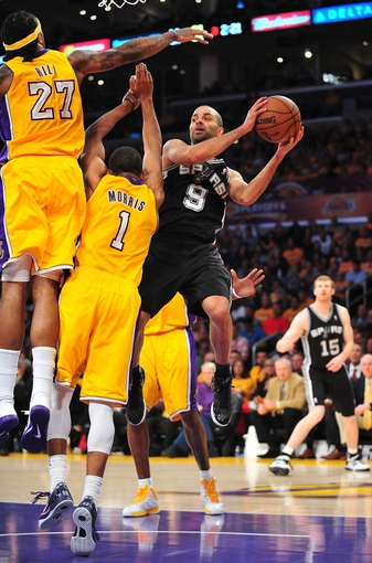 April 26, 2013; Los Angeles, CA, USA; San Antonio Spurs point guard Tony Parker (9) passes the ball against the defense of Los Angeles Lakers center Jordan Hill (27) and point guard Darius Morris (1) during the second half in game three of the first round of the 2013 NBA playoffs at Staples Center. Mandatory Credit: Gary A. Vasquez-USA TODAY Sports