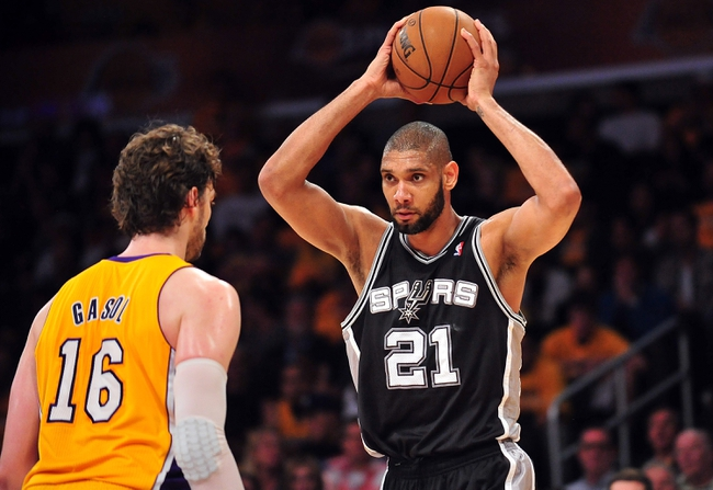 April 26, 2013; Los Angeles, CA, USA; San Antonio Spurs power forward Tim Duncan (21) controls the ball against the defense of Los Angeles Lakers power forward Pau Gasol (16) during the second half in game three of the first round of the 2013 NBA playoffs at Staples Center. Mandatory Credit: Gary A. Vasquez-USA TODAY Sports