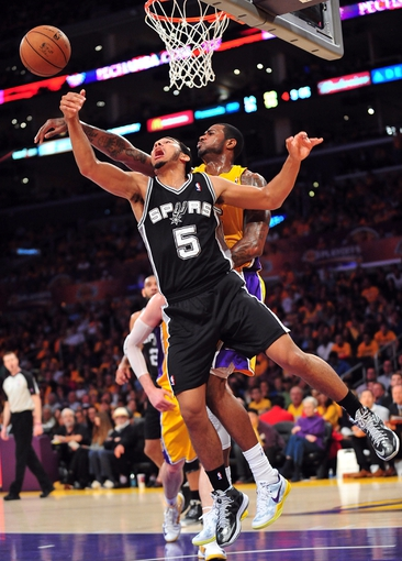 April 26, 2013; Los Angeles, CA, USA; San Antonio Spurs point guard Cory Joseph (5) is blocked on a scoring attempt by Los Angeles Lakers small forward Earl Clark (6) during the second half in game three of the first round of the 2013 NBA playoffs at Staples Center. Mandatory Credit: Gary A. Vasquez-USA TODAY Sports