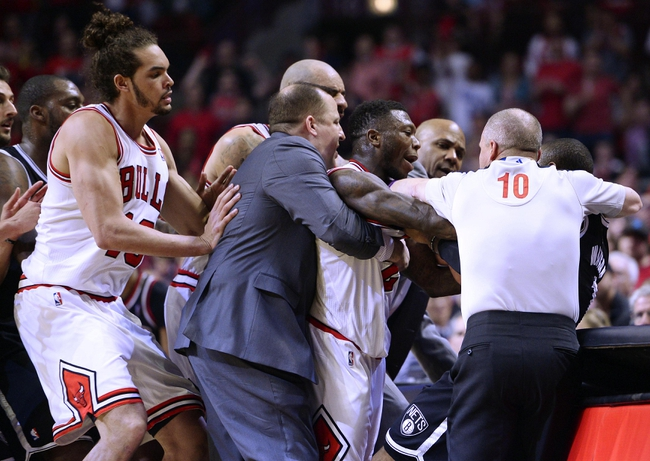 Apr 27, 2013; Chicago, IL, USA; Chicago Bulls head coach Tom Thibodeau attempts to separate point guard Nate Robinson (2) from Brooklyn Nets point guard C.J. Watson (1) in the second quarter during game four of the first round of the 2013 NBA playoffs at the United Center. Mandatory Credit: Mike DiNovo-USA TODAY Sports