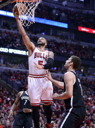 Apr 27, 2013; Chicago, IL, USA; Chicago Bulls power forward Carlos Boozer (5) shoots the ball over Brooklyn Nets center Brook Lopez (11) in the second quarter during game four of the first round of the 2013 NBA playoffs at the United Center. Mandatory Credit: Mike DiNovo-USA TODAY Sports
