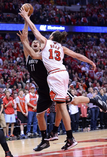 Apr 27, 2013; Chicago, IL, USA; Brooklyn Nets center Brook Lopez (11) shoots the ball against Chicago Bulls center Joakim Noah (13) in the second half during game four of the first round of the 2013 NBA playoffs at the United Center. Chicago defeats Brooklyn 142-134 in triple overtime. Mandatory Credit: Mike DiNovo-USA TODAY Sports