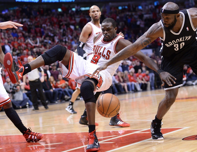 Apr 27, 2013; Chicago, IL, USA; Chicago Bulls small forward Luol Deng (9) is fouled by Brooklyn Nets power forward Reggie Evans (30) in the second half during game four of the first round of the 2013 NBA playoffs at the United Center. Chicago defeats Brooklyn 142-134 in triple overtime. Mandatory Credit: Mike DiNovo-USA TODAY Sports