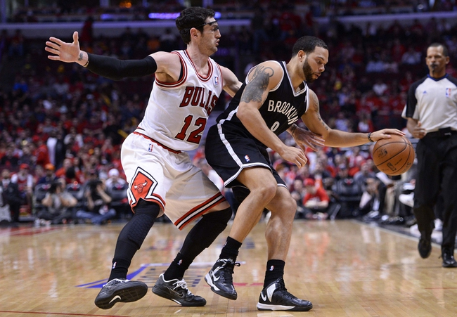 Apr 27, 2013; Chicago, IL, USA; Brooklyn Nets point guard Deron Williams (8) dribbles the ball against Chicago Bulls shooting guard Kirk Hinrich (12) in the second half during game four of the first round of the 2013 NBA playoffs at the United Center. Chicago defeats Brooklyn 142-134 in triple overtime. Mandatory Credit: Mike DiNovo-USA TODAY Sports