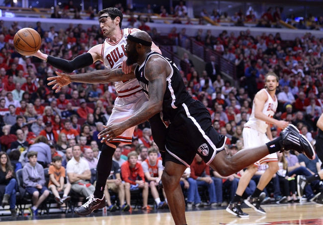Apr 27, 2013; Chicago, IL, USA; Chicago Bulls shooting guard Kirk Hinrich (12) attempts to get a loose ball against Brooklyn Nets power forward Reggie Evans (30) in the second half during game four of the first round of the 2013 NBA playoffs at the United Center. Chicago defeats Brooklyn 142-134 in triple overtime. Mandatory Credit: Mike DiNovo-USA TODAY Sports