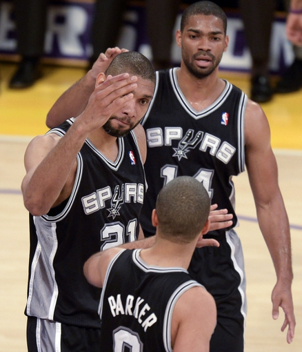 Apr 28, 2013; Los Angeles, CA, USA; San Antonio Spurs power forward Tim Duncan (21) high-fives teammate Tony Parker on the back of the head after he scored against the Lakers in 1st half action in game four of the first round of the 2013 NBA playoffs at the Staples Center. The Spurs won 103-82 and eliminated the Lakers. In the background is San Antonio Spurs power forward Aron Baynes (16). Mandatory Credit: Robert Hanashiro-USA TODAY Sports