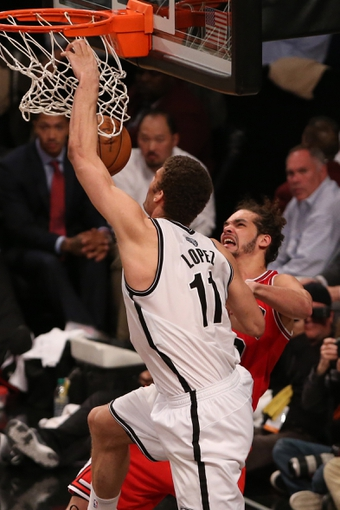 Apr 29, 2013; Brooklyn, NY, USA; Chicago Bulls center Joakim Noah (13) fouls Brooklyn Nets center Brook Lopez (11) at the net during the fourth quarter in game five of the first round of the 2013 NBA playoffs at the Barclays Center. Brooklyn won 110-91.  Mandatory Credit: Anthony Gruppuso-USA TODAY Sports