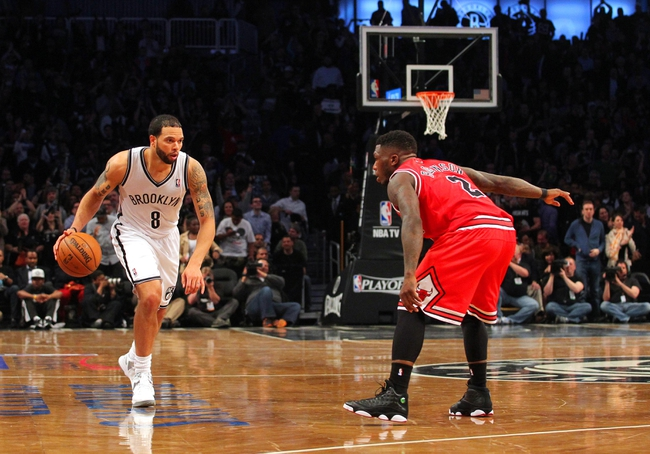 Apr 29, 2013; Brooklyn, NY, USA; Brooklyn Nets guard Deron Williams (8) controls the ball against Chicago Bulls guard Nate Robinson (2) during the fourth quarter of game five of the first round of the 2013 NBA playoffs at the Barclays Center. Mandatory Credit: Brad Penner-USA TODAY Sports