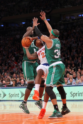 May 1, 2013; New York, NY, USA; New York Knicks forward Iman Shumpert (21) is defended by Boston Celtics center Kevin Garnett (5) and forward Paul Pierce (34) during the fourth quarter of game five of the first round of the 2013 NBA Playoffs at Madison Square Garden. Mandatory Credit: Brad Penner-USA TODAY Sports