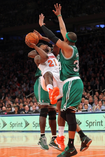 May 1, 2013; New York, NY, USA; New York Knicks forward Iman Shumpert (21) is defended by Boston Celtics center Kevin Garnett (5) and Boston Celtics forward Paul Pierce (34) during the fourth quarter of game five of the first round of the 2013 NBA Playoffs at Madison Square Garden. Mandatory Credit: Brad Penner-USA TODAY Sports