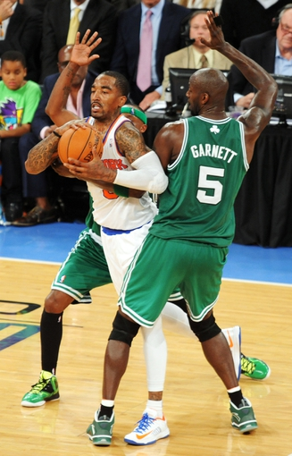 May 1, 2013; New York, NY, USA; New York Knicks shooting guard J.R. Smith (8) protects the ball from Boston Celtics center Kevin Garnett (5) and shooting guard Jason Terry (4) during the second half in game five of the first round of the 2013 NBA Playoffs at Madison Square Garden. The Celtics won the game 92-86. Mandatory Credit: Joe Camporeale-USA TODAY Sports