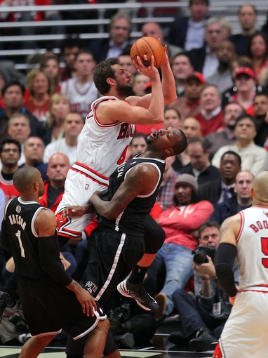 May 2, 2013; Chicago, IL, USA; Chicago Bulls shooting guard Marco Belinelli (8) is fouled by Brooklyn Nets center Andray Blatche (0) during the first half in game six of the first round of the 2013 NBA Playoffs at the United Center. Mandatory Credit: Dennis Wierzbicki-USA TODAY Sports