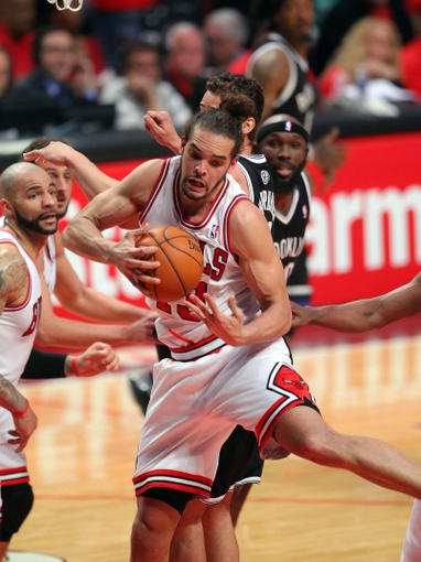 May 2, 2013; Chicago, IL, USA; Chicago Bulls center Joakim Noah (13) pulls down a rebound over Brooklyn Nets power forward Kris Humphries (43) during the first half in game six of the first round of the 2013 NBA Playoffs at the United Center. Mandatory Credit: Dennis Wierzbicki-USA TODAY Sports