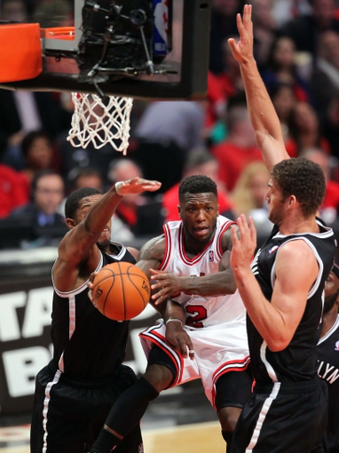 May 2, 2013; Chicago, IL, USA; Chicago Bulls point guard Nate Robinson (center) drives between Brooklyn Nets shooting guard Joe Johnson (left) and center Brook Lopez (right) during the second half in game six of the first round of the 2013 NBA Playoffs at the United Center. Brooklyn won 95-92. Mandatory Credit: Dennis Wierzbicki-USA TODAY Sports
