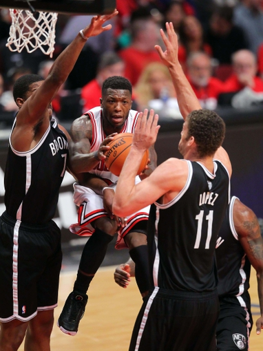 May 2, 2013; Chicago, IL, USA; Chicago Bulls point guard Nate Robinson (center) drives between Brooklyn Nets shooting guard Joe Johnson (left) and Brooklyn Nets center Brook Lopez (right) during the second half in game six of the first round of the 2013 NBA Playoffs at the United Center. Brooklyn won 95-92. Mandatory Credit: Dennis Wierzbicki-USA TODAY Sports