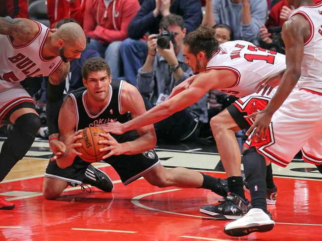 May 2, 2013; Chicago, IL, USA; Brooklyn Nets center Brook Lopez (center) battles for the ball with Chicago Bulls power forward Carlos Boozer (left) and Chicago Bulls center Joakim Noah (right) during the second half in game six of the first round of the 2013 NBA Playoffs at the United Center. Brooklyn won 95-92. Mandatory Credit: Dennis Wierzbicki-USA TODAY Sports