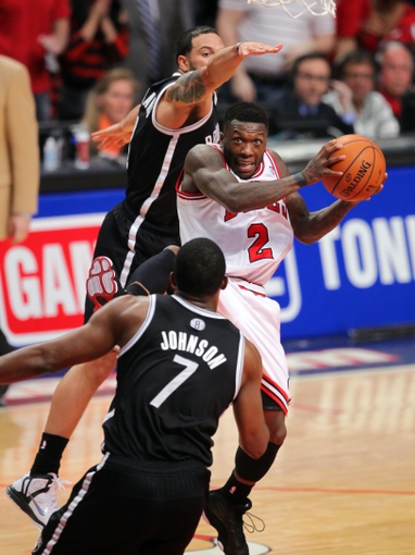 May 2, 2013; Chicago, IL, USA; Chicago Bulls point guard Nate Robinson (center) drives between Brooklyn Nets point guard Deron Williams (back) and Brooklyn Nets shooting guard Joe Johnson (front) during the second half in game six of the first round of the 2013 NBA Playoffs at the United Center. Brooklyn won 95-92. Mandatory Credit: Dennis Wierzbicki-USA TODAY Sports