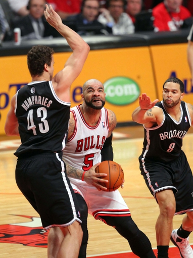 May 2, 2013; Chicago, IL, USA; Chicago Bulls power forward Carlos Boozer (center) drives between Brooklyn Nets power forward Kris Humphries (left) and point guard Deron Williams (right) during the second half in game six of the first round of the 2013 NBA Playoffs at the United Center. Brooklyn won 95-92. Mandatory Credit: Dennis Wierzbicki-USA TODAY Sports