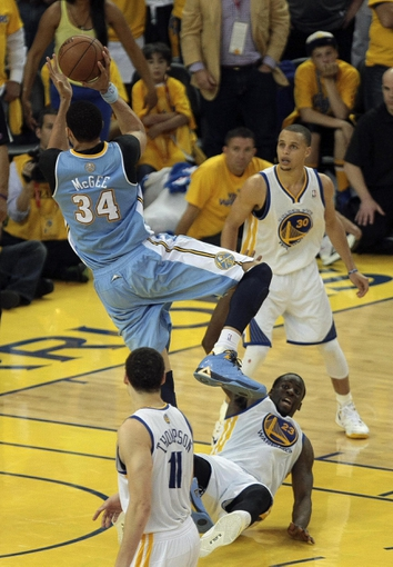 May 2, 2013; Oakland, CA, USA; Golden State Warriors small forward Draymond Green (23) fouls Denver Nuggets center JaVale McGee (34) on the shot during the fourth quarter of game six of the first round of the 2013 NBA Playoffs at Oracle Arena. The Golden State Warriors defeated the Denver Nuggets 92-88 to win the series. Mandatory Credit: Kelley L Cox-USA TODAY Sports