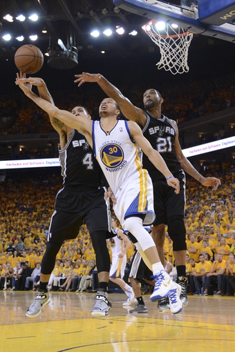 May 12, 2013; Oakland, CA, USA; Golden State Warriors point guard Stephen Curry (30) drives to the basket against San Antonio Spurs shooting guard Danny Green (4) and power forward Tim Duncan (21) during the fourth quarter in game four of the second round of the 2013 NBA Playoffs at Oracle Arena. The Warriors defeated the Spurs 97-87 in overtime. Mandatory Credit: Kyle Terada-USA TODAY Sports