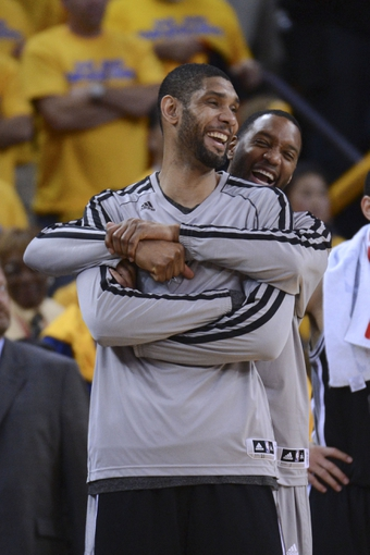 May 16, 2013; Oakland, CA, USA; San Antonio Spurs shooting guard Tracy McGrady (1, back) hugs power forward Tim Duncan (21, front) during the fourth quarter in game six of the second round of the 2013 NBA Playoffs against the Golden State Warriors at Oracle Arena. The Spurs defeated the Warriors 94-82.  Mandatory Credit: Kyle Terada-USA TODAY Sports