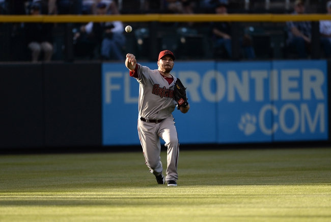 May 21, 2013; Denver, CO, USA; Arizona Diamondbacks left fielder Jason Kubel (13) throws back to third base in the second inning against the Colorado Rockies at Coors Field. Mandatory Credit: Ron Chenoy-USA TODAY Sports