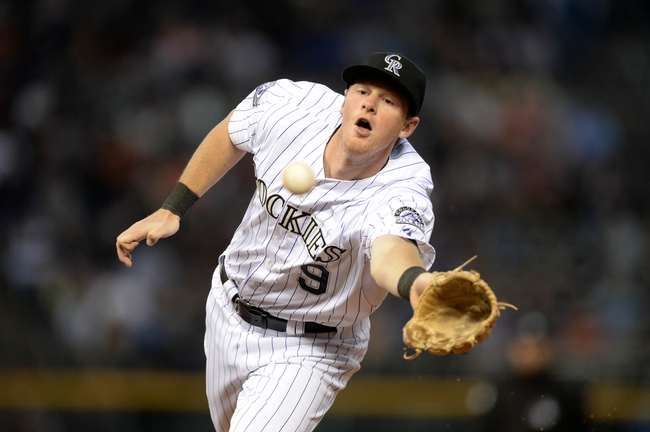 May 21, 2013; Denver, CO, USA; Colorado Rockies second baseman DJ LeMahieu (9) uses his glove to toss back to first base for an out during the game against the Arizona Diamondbacks at Coors Field. The Rockies defeated the Diamondback 5-4 in ten innings. Mandatory Credit: Ron Chenoy-USA TODAY Sports