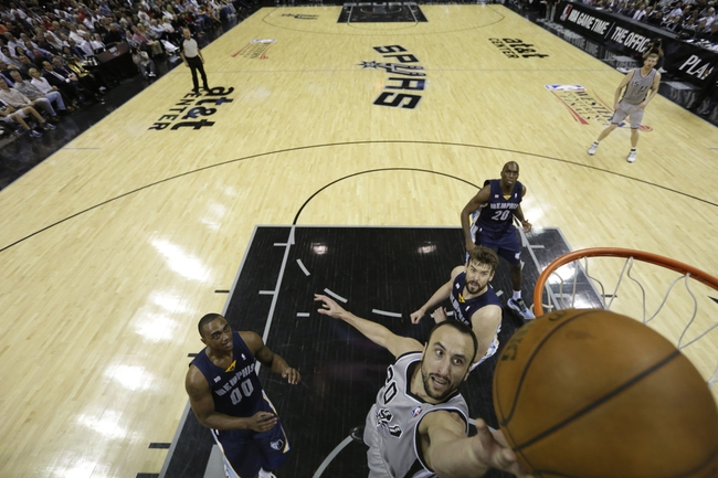 May 21, 2013; San Antonio, TX, USA; San Antonio Spurs guard Manu Ginobili (20) drives to the basket as Memphis Grizzlies forward Darrell Arthur (00) looks on  game two of the Western Conference finals of the 2013 NBA Playoffs against the Memphis Grizzlies at AT&T Center. Mandatory Credit: Ronald Martinez/Getty Images-Pool Photo via USA TODAY Sports