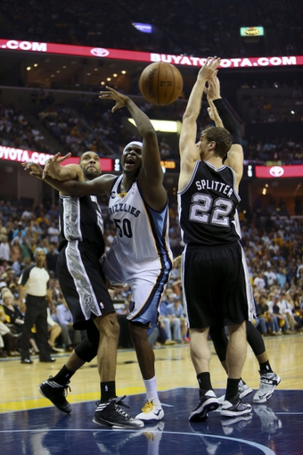 May 25, 2013; Memphis, TN, USA; Memphis Grizzlies power forward Zach Randolph (50) reaches out for the rebound while guarded by San Antonio Spurs power forward Tim Duncan (21) and San Antonio Spurs center Tiago Splitter (22) in game three of the Western Conference finals of the 2013 NBA Playoffs at FedEx Forum. San Antonio Spurs defeat the Memphis Grizzlies 104-93, and lead the series 3-0.  Mandatory Credit: Spruce Derden-USA TODAY Sports