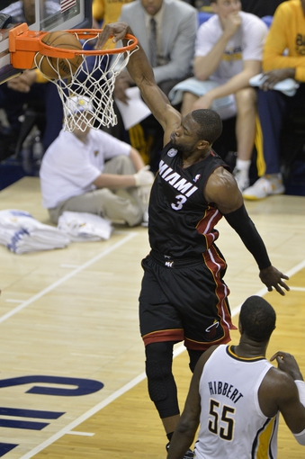 May 26, 2013; Indianapolis, IN, USA; Miami Heat shooting guard Dwyane Wade (3) dunks over Indiana Pacers center Roy Hibbert (55) during the third quarter in game three of the Eastern Conference finals of the 2013 NBA Playoffs at Bankers Life Fieldhouse. Mandatory Credit: Jamie Rhodes-USA TODAY Sports