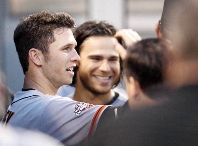 Jun 13, 2013; Pittsburgh, PA, USA; San Francisco Giants catcher Buster Posey (left) reacts in the dugout after scoring a run against the Pittsburgh Pirates during the fifth inning at PNC Park. Mandatory Credit: Charles LeClaire-USA TODAY Sports