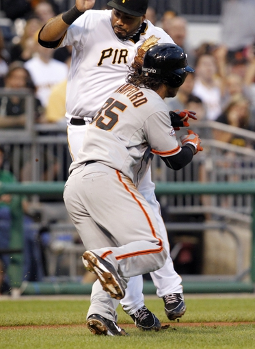 Jun 13, 2013; Pittsburgh, PA, USA; San Francisco Giants shortstop Brandon Crawford (35) runs into Pittsburgh Pirates third baseman Pedro Alvarez (rear) on a run down during the fifth inning at PNC Park. Crawford scored as Alvarez was called for interference on the play. Mandatory Credit: Charles LeClaire-USA TODAY Sports