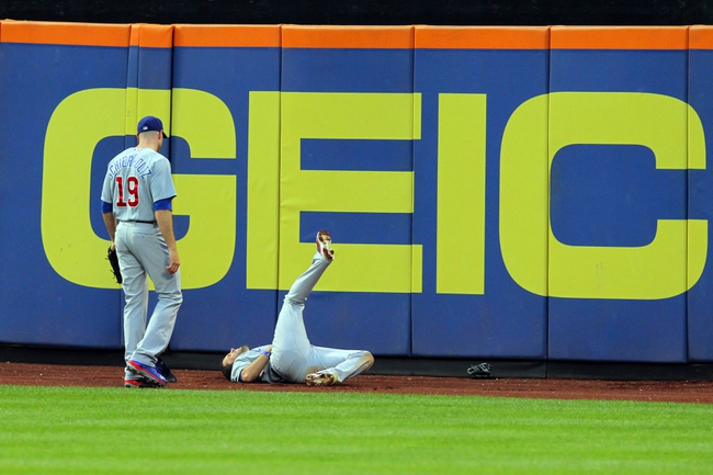 Jun 14, 2013; New York, NY, USA; Chicago Cubs center fielder David DeJesus (9) lays on the ground after running into the wall chasing a triple by New York Mets center fielder Juan Lagares (not pictured) during the third inning of a game at Citi Field. Mandatory Credit: Brad Penner-USA TODAY Sports