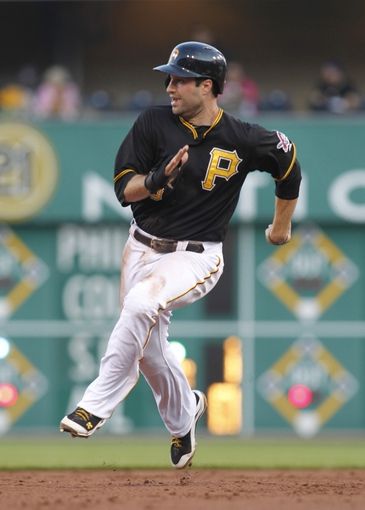 Jun 14, 2013; Pittsburgh, PA, USA; Pittsburgh Pirates second baseman Neil Walker (18) runs between second and third base against the Los Angeles Dodgers during the third inning at PNC Park. Mandatory Credit: Charles LeClaire-USA TODAY Sports