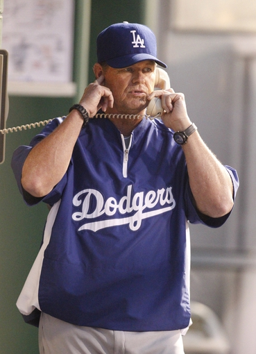 Jun 14, 2013; Pittsburgh, PA, USA; Los Angeles Dodgers pitching coach Rick Honeycutt (40) makes a call to the bullpen from the dugout against the Pittsburgh Pirates during the seventh inning at PNC Park. The Pittsburgh Pirates won 3-0. Mandatory Credit: Charles LeClaire-USA TODAY Sports