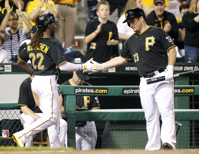Jun 14, 2013; Pittsburgh, PA, USA; Pittsburgh Pirates center fielder Andrew McCutchen (22) is greeted at the dugout by right fielder Travis Snider (23) after McCutchen scored a run against the Los Angeles Dodgers during the eighth inning at PNC Park. The Pittsburgh Pirates won 3-0. Mandatory Credit: Charles LeClaire-USA TODAY Sports