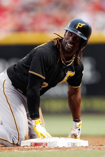Jun 17, 2013; Cincinnati, OH, USA; Pittsburgh Pirates center fielder Andrew McCutchen (22) reacts after diving back to first base during the fourth inning against the Cincinnati Reds at Great American Ball Park. Mandatory Credit: Frank Victores-USA TODAY Sports