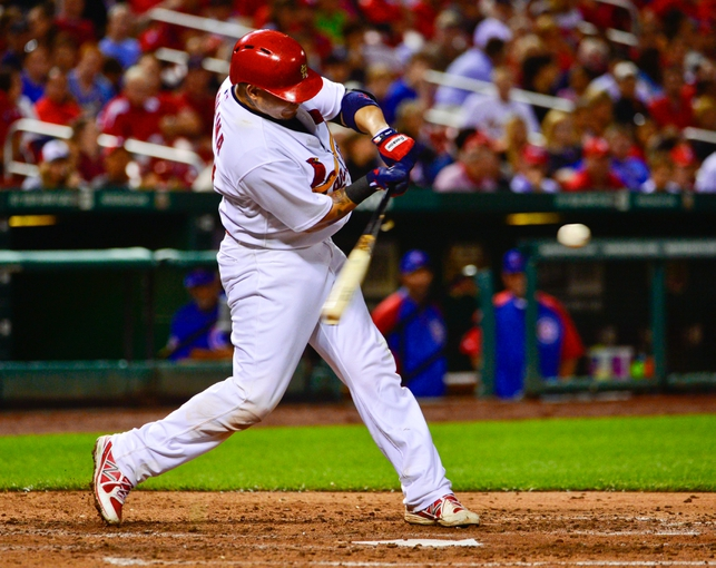 Jun 17, 2013; St. Louis, MO, USA; St. Louis Cardinals catcher Yadier Molina (4) gets a hit against the Chicago Cubs during the seventh inning at Busch Stadium. Mandatory Credit: Scott Rovak-USA TODAY Sports